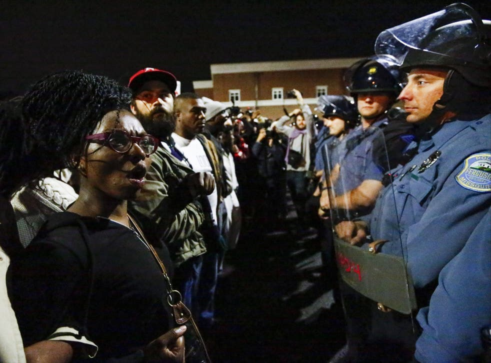 Protestors confront a police line as they march against the recent police shootings outside the Ferguson Police Department headquarters in Missouri