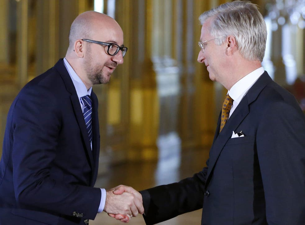 Belgium's new Prime Minister Charles Michel, left, shakes hands with King Philippe after a swearing-in ceremony at the Brussels Royal Palace