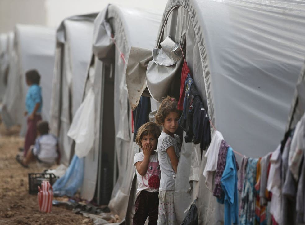 Syrian Kurdish refugee children who fled Kobani with their families stand outside their tent at a refugee camp in Suruc