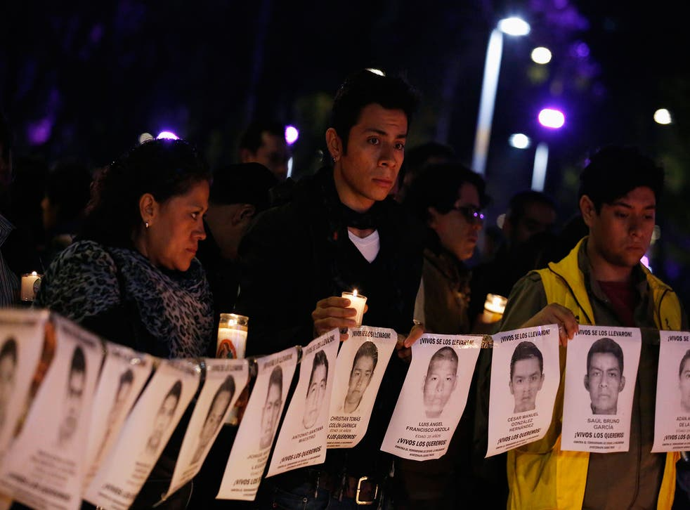 Protesters and members of Amnesty International hold photographs of missing students outside the building of the office of Mexico's Attorney General, during a protest supporting the Ayotzinapa Teacher Training College missing students