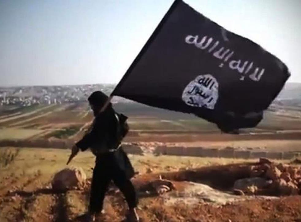 A member of Ussud Al-Anbar, a group that is affiliated to Isis, holding up the black and white flag in Iraq's Anbar province