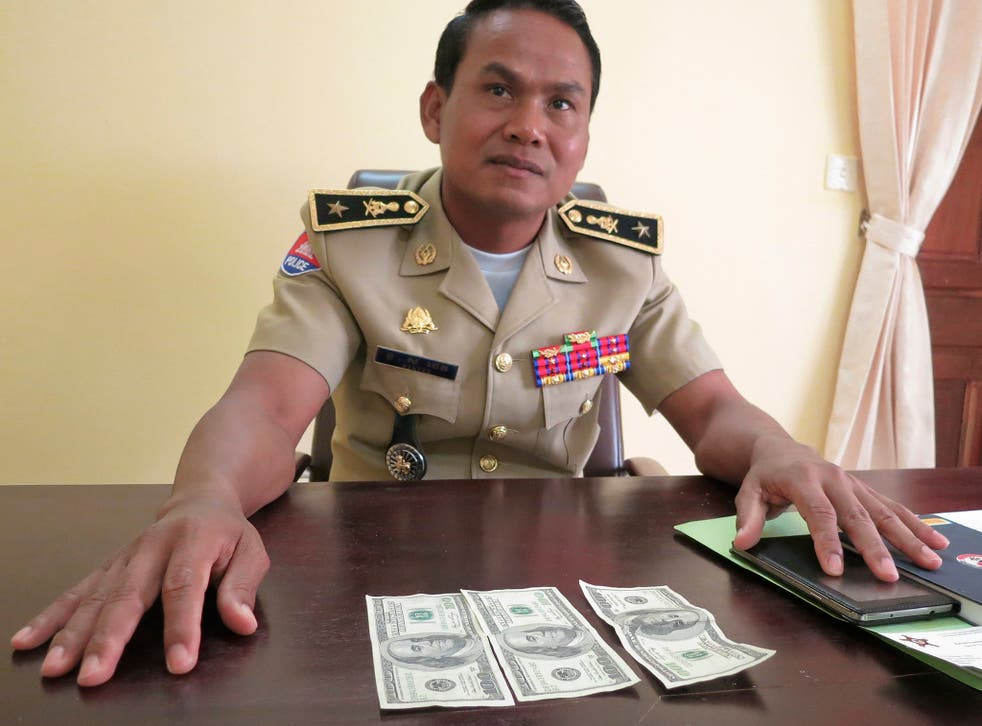 Battambang police chief Brigadier General Sar Theth poses with notes from a seized haul of $7.16 million in counterfeit hundred-dollar bills in Battambang