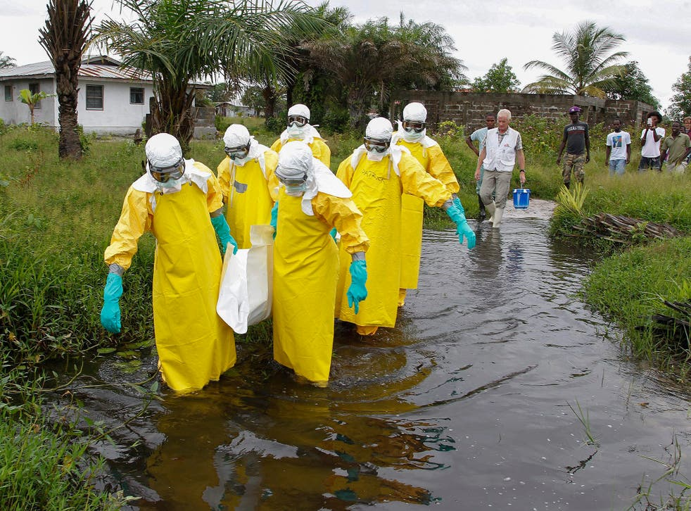 A Liberian burial squad carry the body of an Ebola victim in Marshall, Margini county, Liberia
