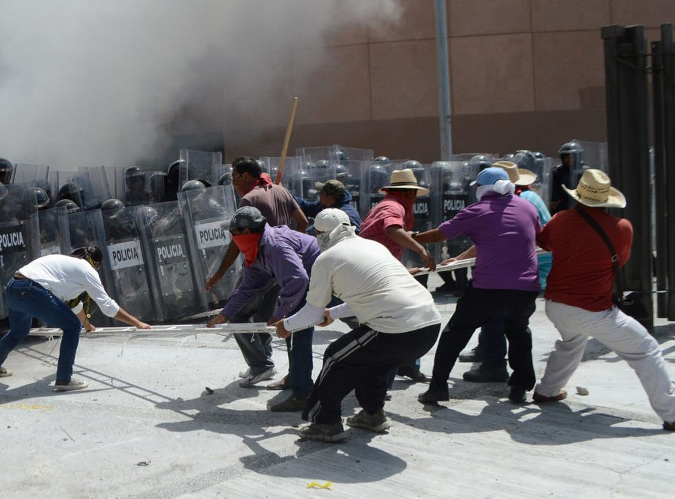 A group of teachers and students and relatives of the 43 Mexican missing students clash with policemen at the Congress of the state of Guerrero to protest the slow advances in the investigation over them, in Chilpancingo, Guerrero. Demonstrators, surround