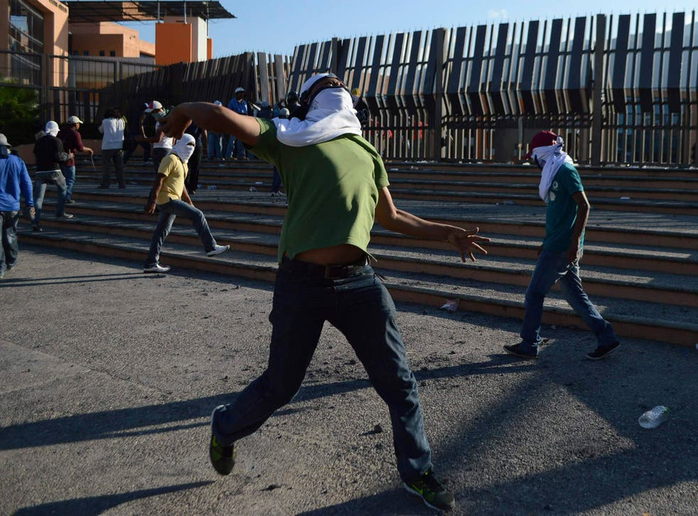 """A student of the Ayotzinapa Teacher Training College """"Raul Isidro Burgos"""" throws a stone during a protest"""