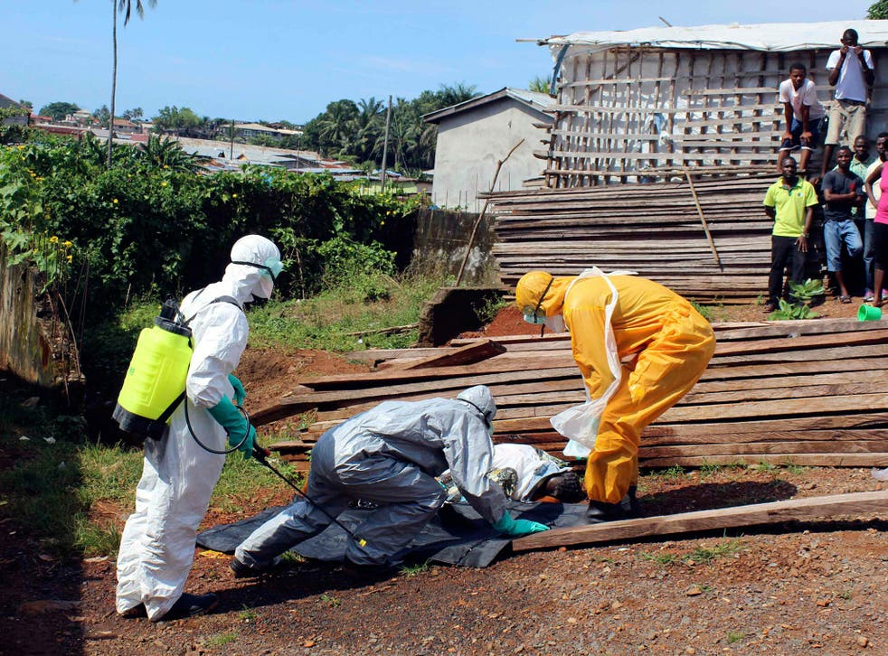 Health workers remove the body a woman who died from the Ebola virus in the Aberdeen district of Freetown, Sierra Leone