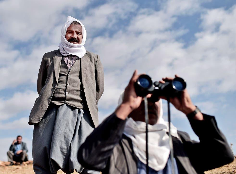Kurdish men look towards Kobani from the Turkish-Syrian border as US-led bombing grows in intensity