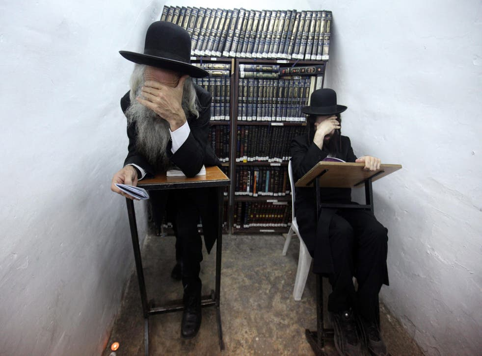 In or out? Ultra-Orthodox Jewish men read from a religious book