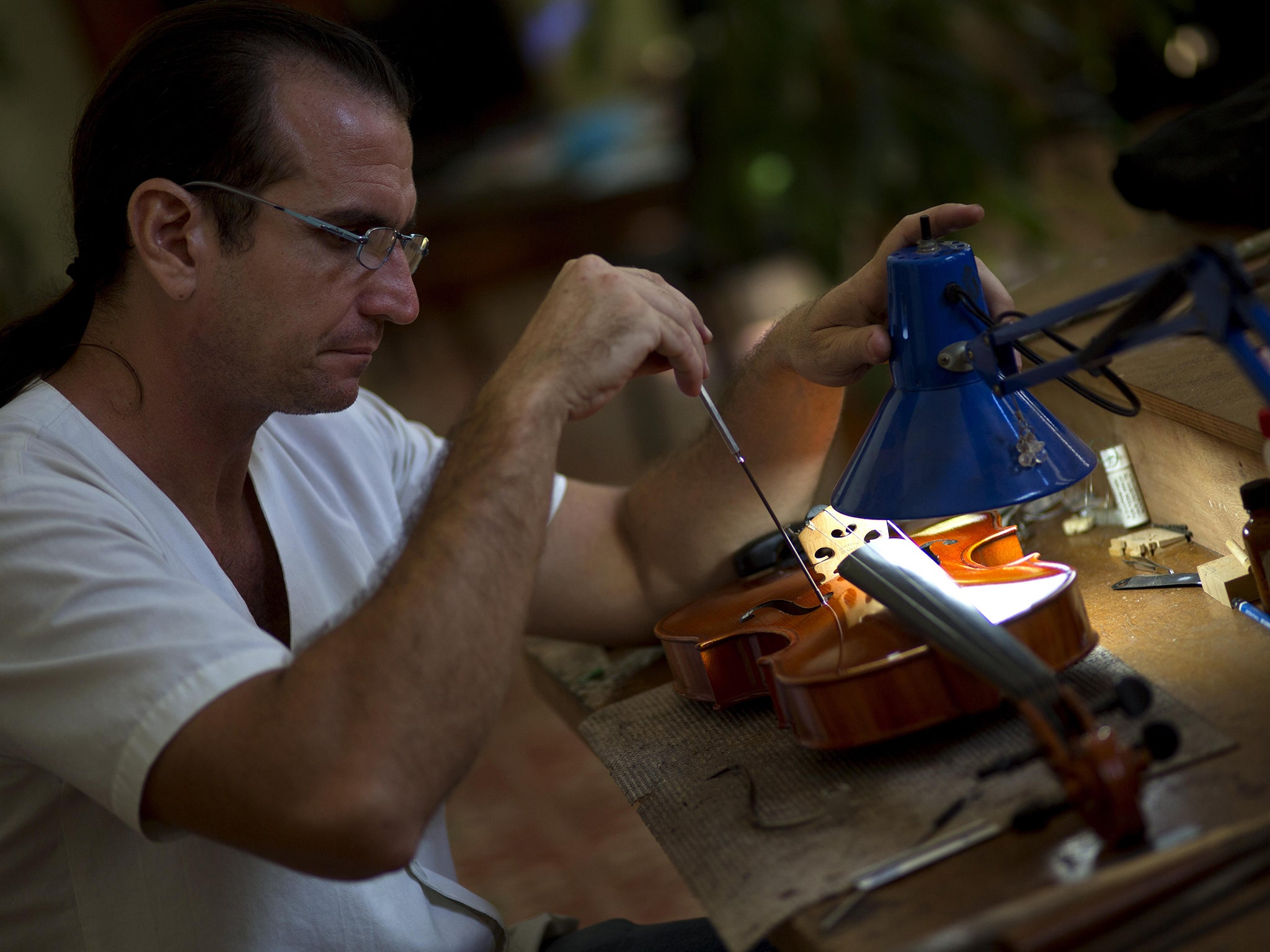 Andres Martinez repairs a viola at his workshop in Havana AP