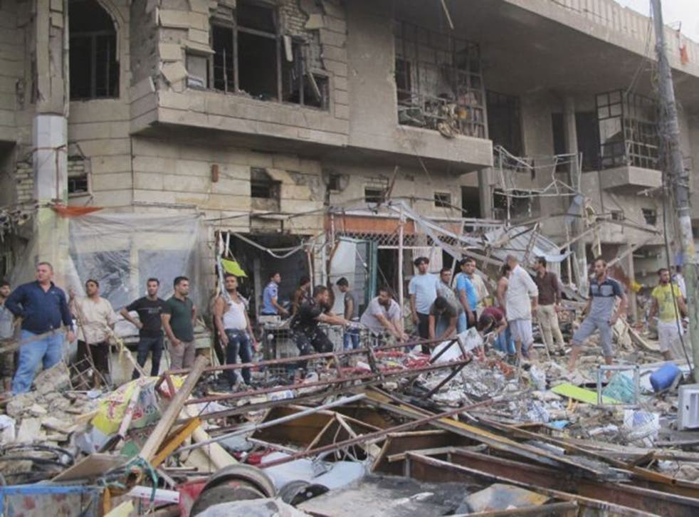 People gather at the site of a car bomb attack in Baghdad, October 16,
