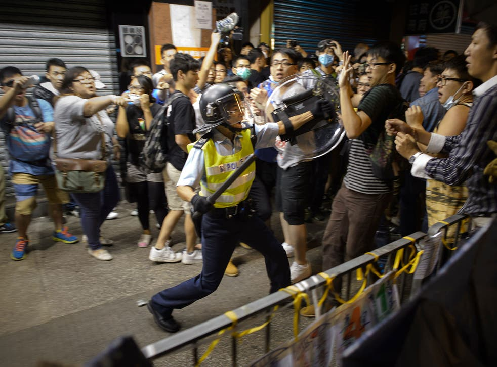 A policeman confronts protesters in the Mong Kok shopping district of Hong Kong