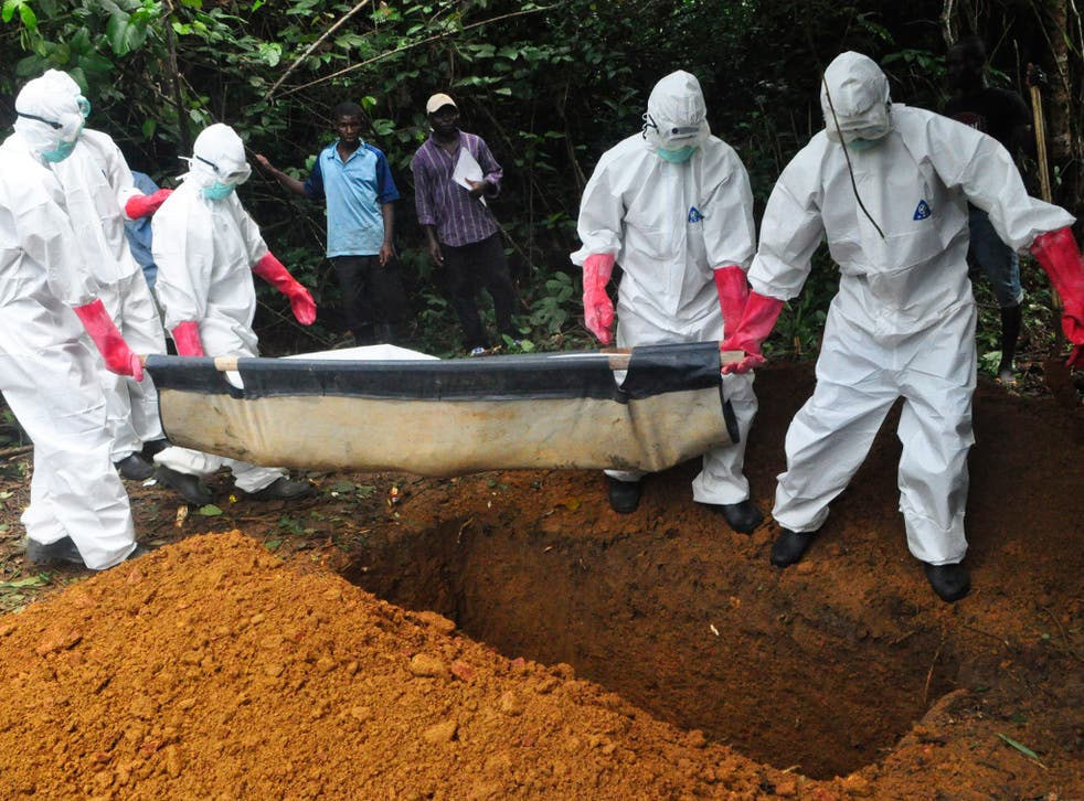 A burial team in protective gear bury the body of a woman suspected to have died from Ebola virus in Monrovia, Liberia