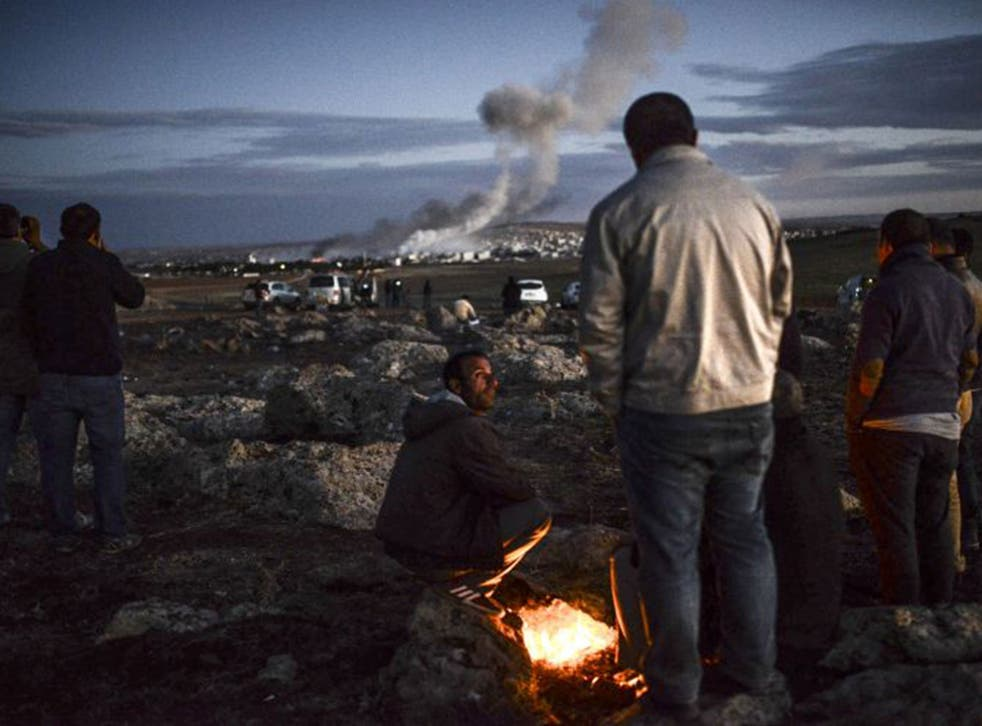 The US and Turkey have stepped up support for Kurdish fighters defending Kobani against Isis but it is still feared the town may fall; above, observers watch the fighting from a nearby village