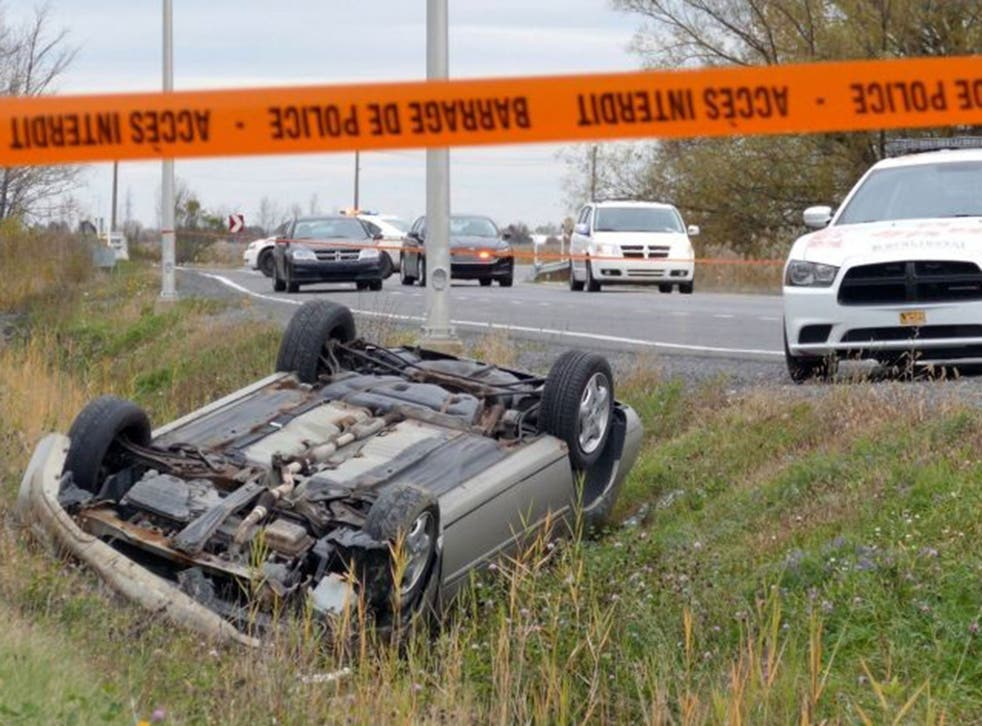 A car is overturned in the ditch in a cordoned off area in St-Jean-sur-Richelieu, Quebec on Monday Oct. 20, 2014.