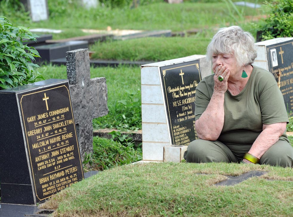 Shirley Shackleton, wife of late journalist Gregory Shackleton, sits next to the grave of the 'Balibo Five' in Jakarta, in 2010