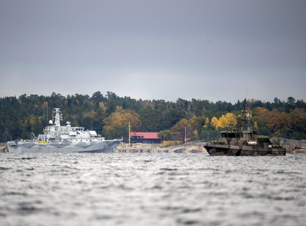 The Swedish minesweeper HMS Kullen, left, and a guard boat in Namdo Bay, Sweden, search for a suspected Russian submarine
