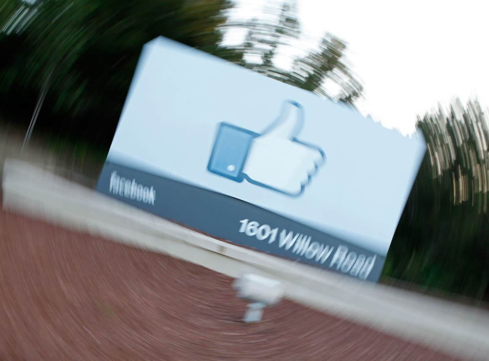 A videographer shoots the side of Facebook's Like Button logo displayed at the entrance of the Facebook Headquarters in Menlo Park, California.