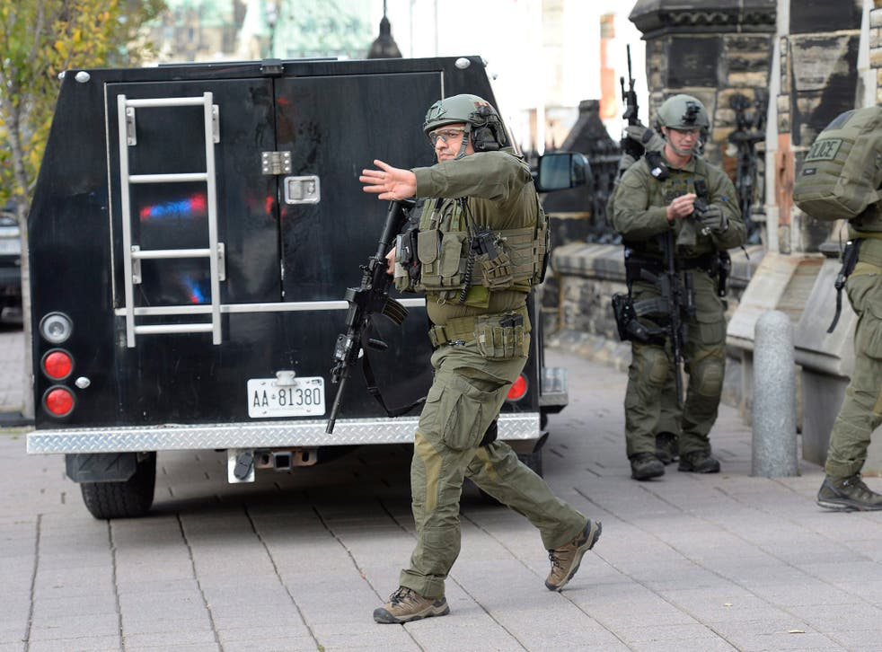 RCMP intervention team members clear the area at the entrance of Parliament hill in Ottawa