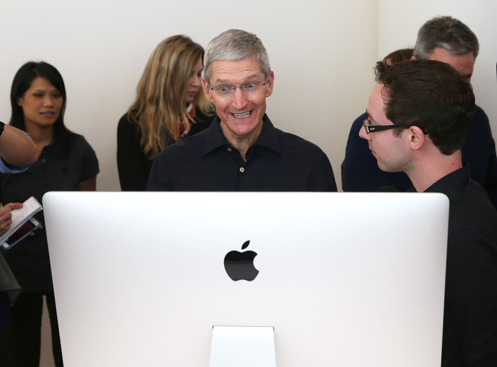 Apple CEO Tim Cook looks at the new 27 inch iMac