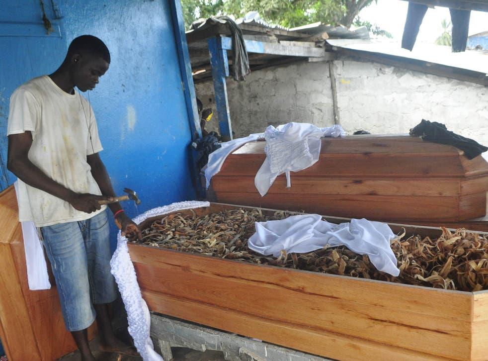 A carpenter makes coffins in New Kru in Monrovia, Liberia