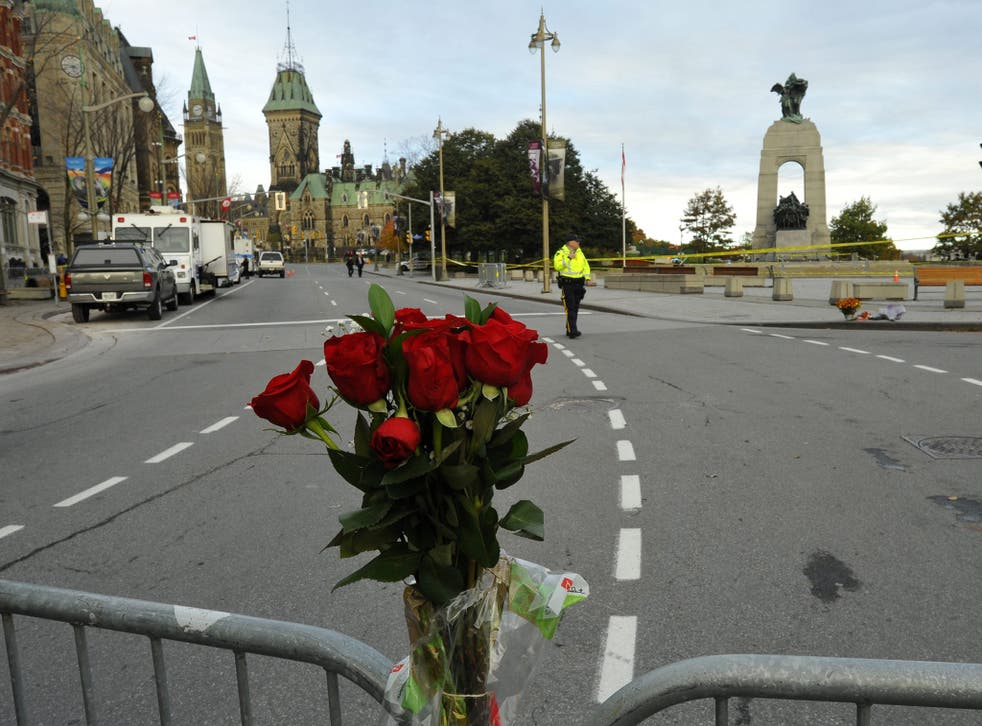 Flowers adorn a barricade around the National War Memorial in Ottawa, Canada