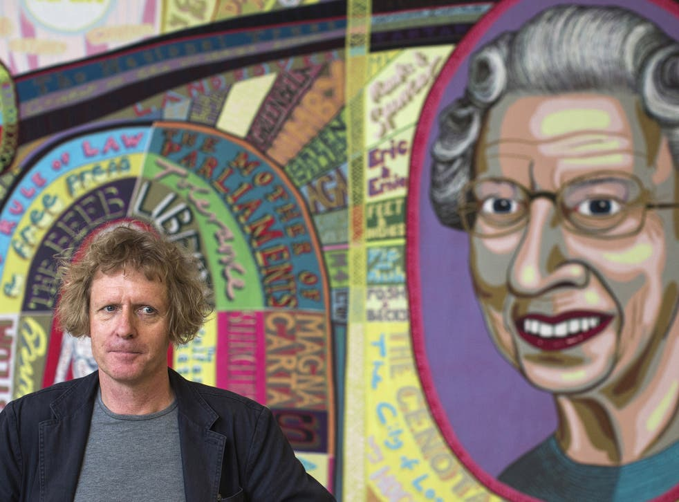 Artist Grayson Perry stands in front of a piece of his entitled 'Comfort Blanket'