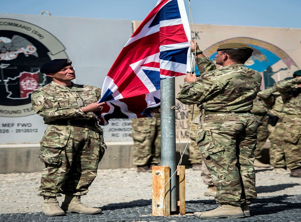 The last Union Flag flying above Helmand Province is lowered by Captain Matthew Clark, left, and Warrant Officer John Lilley