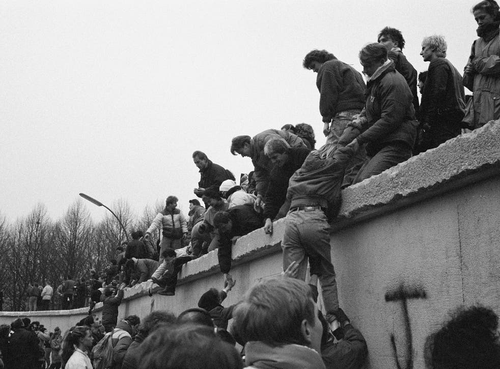 East Berliners climb onto the Berlin Wall to celebrate the effective end of the city's partition on 31st December 1989