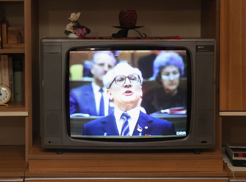 Footage of Erich Honecker delivering a speech is shown on a television in a faithfully-reconstructed typical East German home