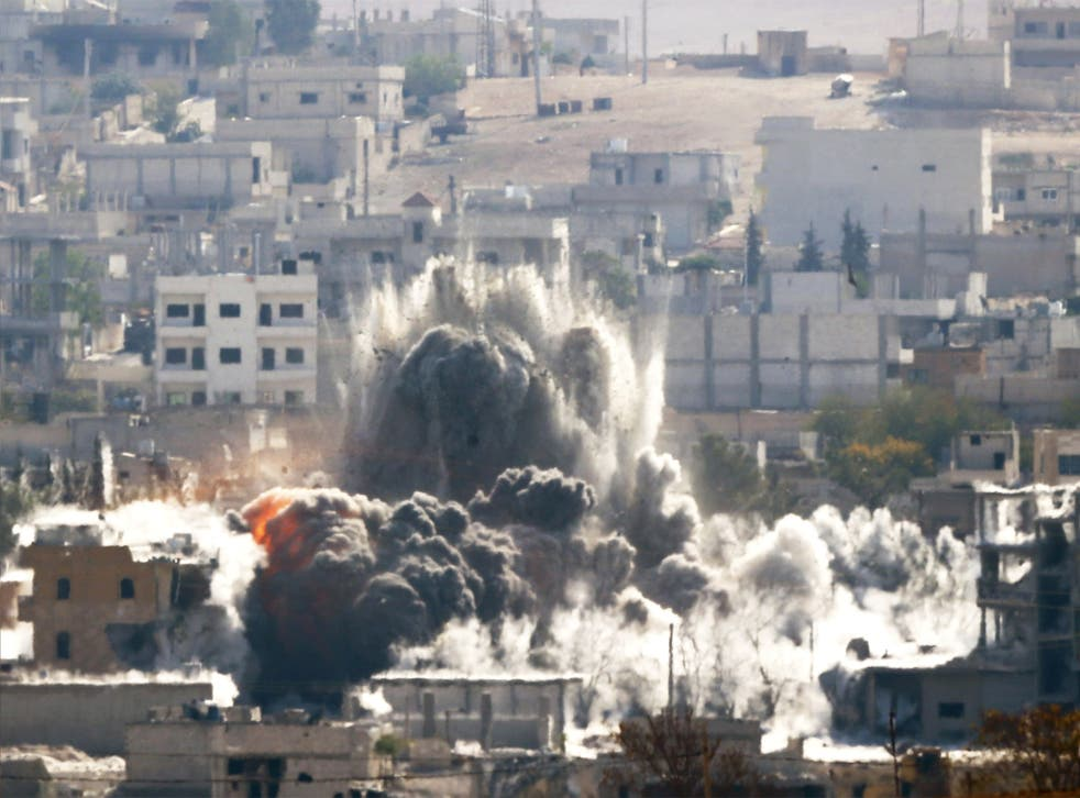 An explosion following an air-strike is seen in the Syrian town of Kobani
