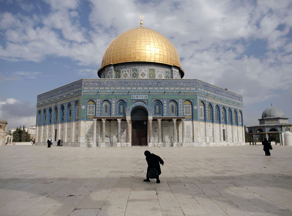 A Palestinian woman walks in front of the Dome of the Rock in the Al-Aqsa mosque compound on October 19, 2014