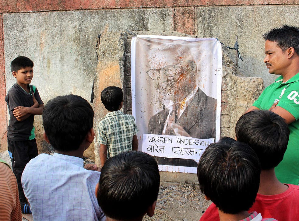 Children of gas victims looking at a defaced poster of Warren Anderson hanging on the wall of the abandoned Union Carbide plant in Bhopal after the news of his death