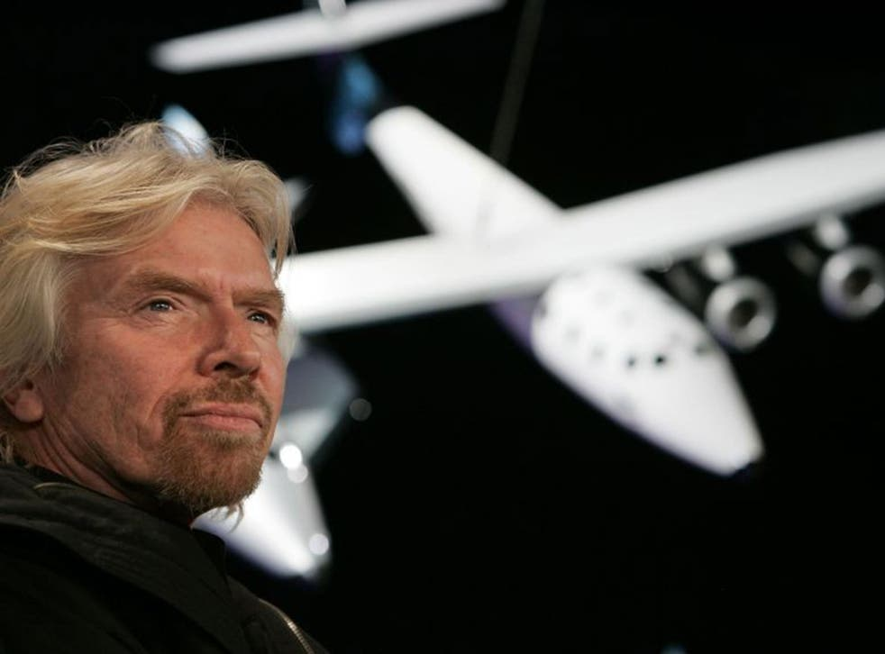 Sir Richard Branson, founder of Virgin Galactic, with a scale model of the  Spaceship Two attached to the White Knight carrier aircraft in this January 2008 photograph