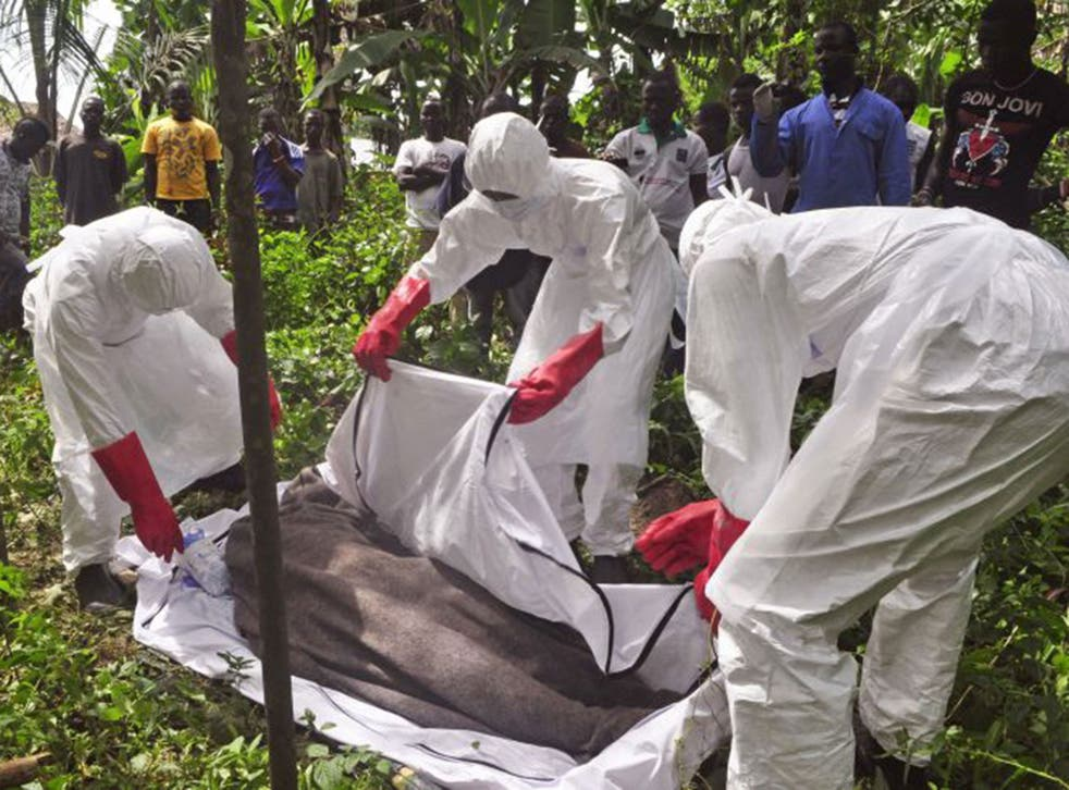 Health workers in Monrovia, Liberia, recover the body of a suspected Ebola victim