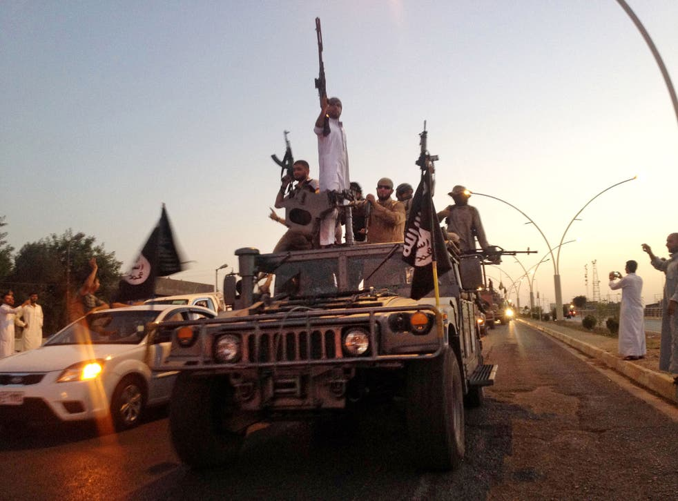 In this file photo taken Monday, June 23, 2014, militants from the Islamic State parade in a commandeered Iraqi security forces armored vehicle on a main street in Mosul, Iraq