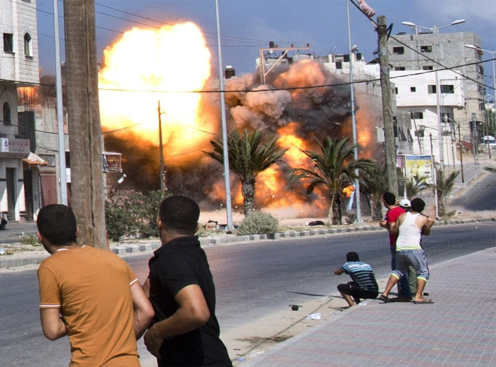 Palestinian men look on as a bomb from an Israeli air strike hits a house in Gaza City in August