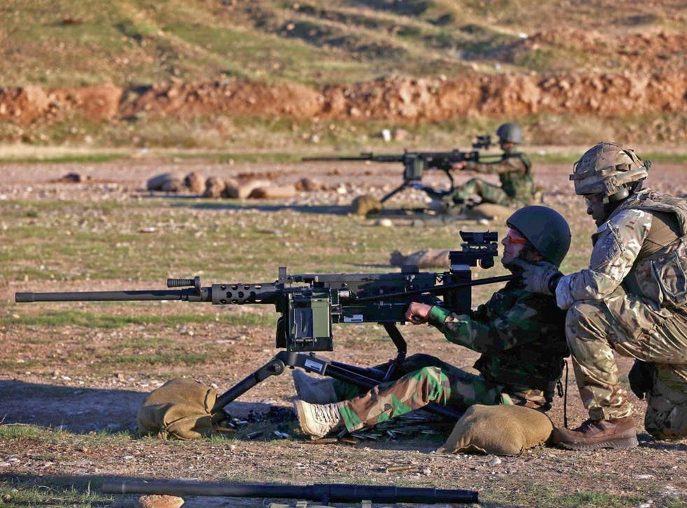 British military advisers instruct Kurdish Peshmerga fighters during a training session at a shooting range in Arbil