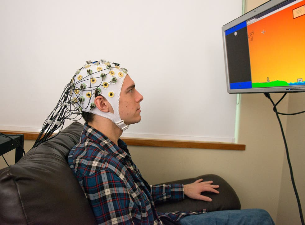 Student Darby Losey thinks about firing a cannon at various points throughout a computer game, whilst an an electroencephalography machine conveys his brain's signals directly to the brain of the receiver