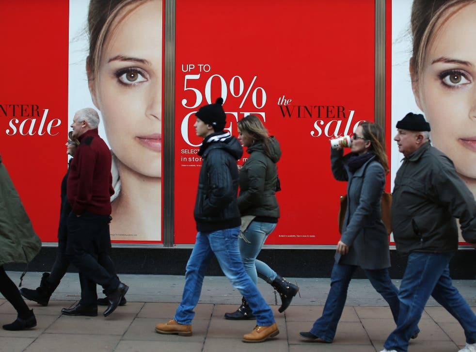 Shoppers walk past a sales sign on Oxford Street