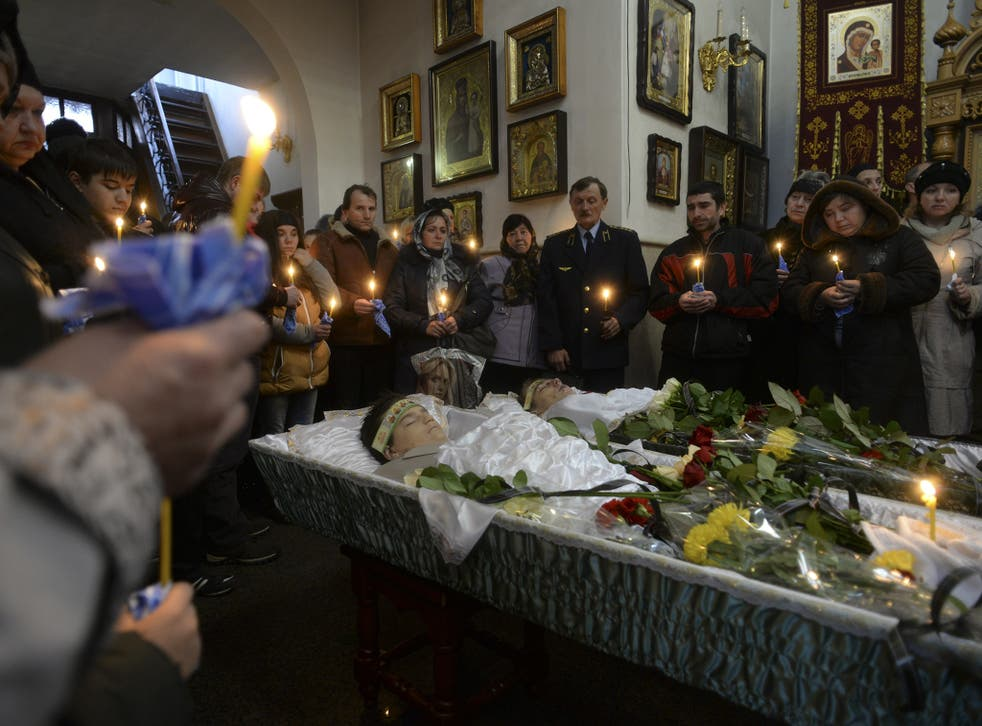 Families, teachers and schoolmates of 18-year-old Andrei Yeliseyev and 14-year-old Daniil Kuznetsov pray during a mourning ceremony in an Orthodox church in Donetsk