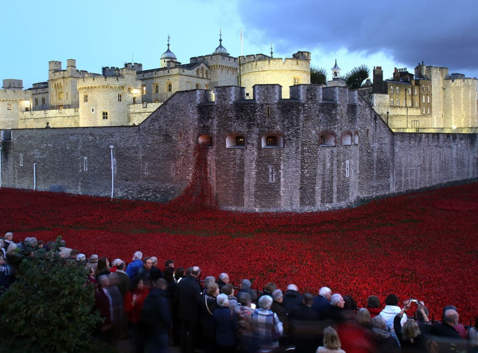 Members of the public stop to look at the ceramic poppies which form part of the art installation 'Blood Swept Lands and Seas of Red' by artist Paul Cummins