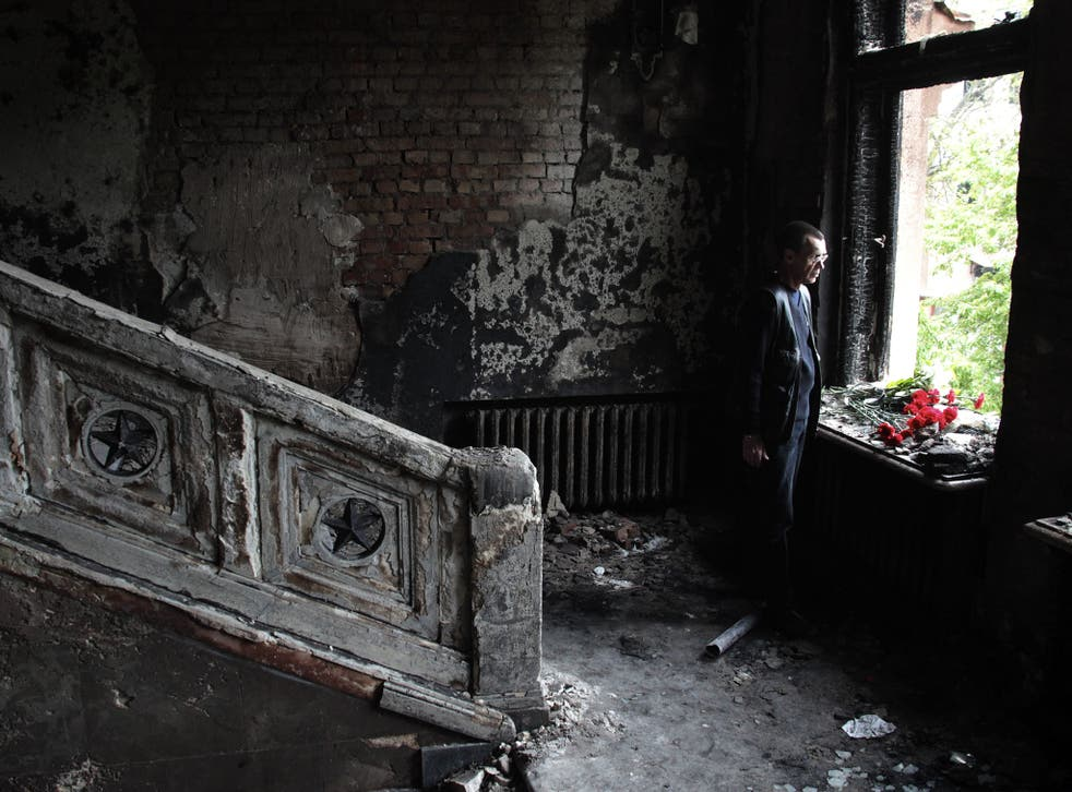 A man lays flowers inside the burnt trade union building in Odessa, Ukraine, where more than 50 people died following a series of riots