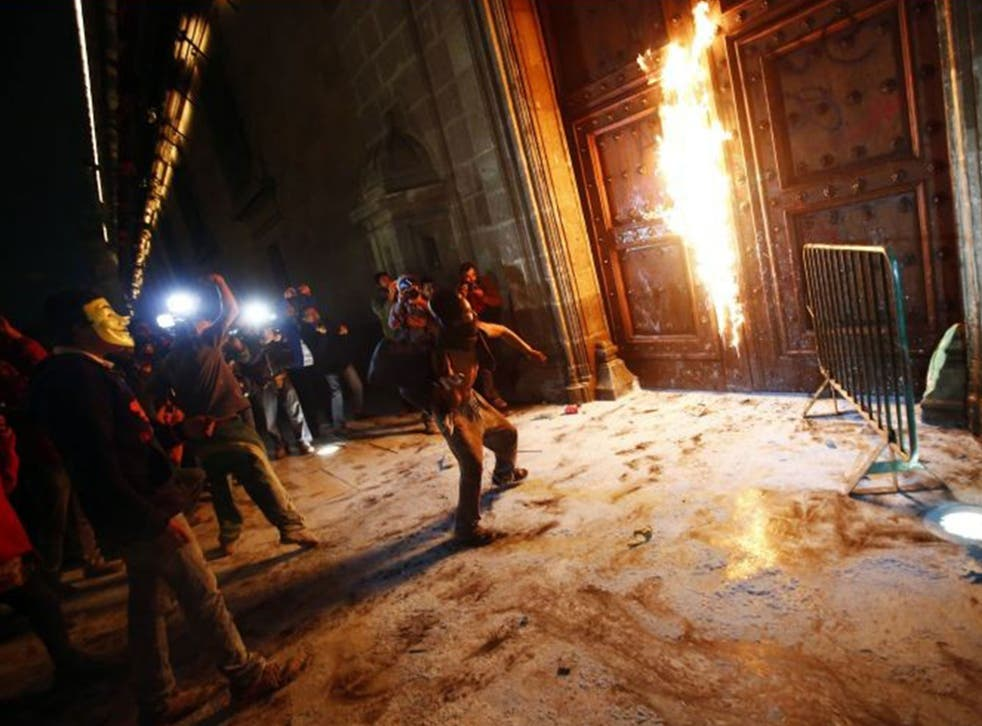 A group of protesters set fire to the wooden door of Mexican President Enrique Pena Nieto's ceremonial palace
