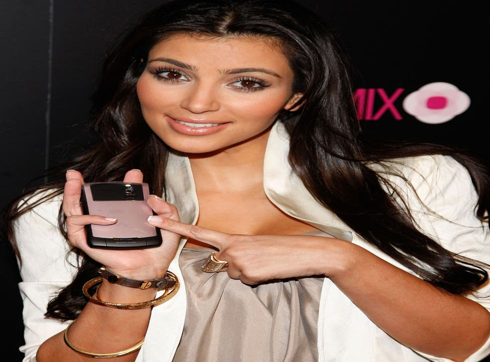Television personality Kim Kardashian poses next to a BlackBerry 8330 Pink Curve xxclusively on August 27, 2008