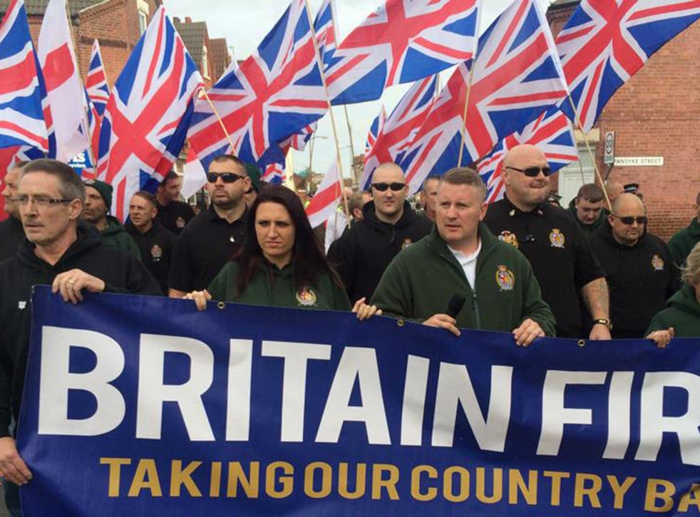 Britain First marching at a rally - Jayda Fransen, in green, can be seen with party leader Paul Golding at the front