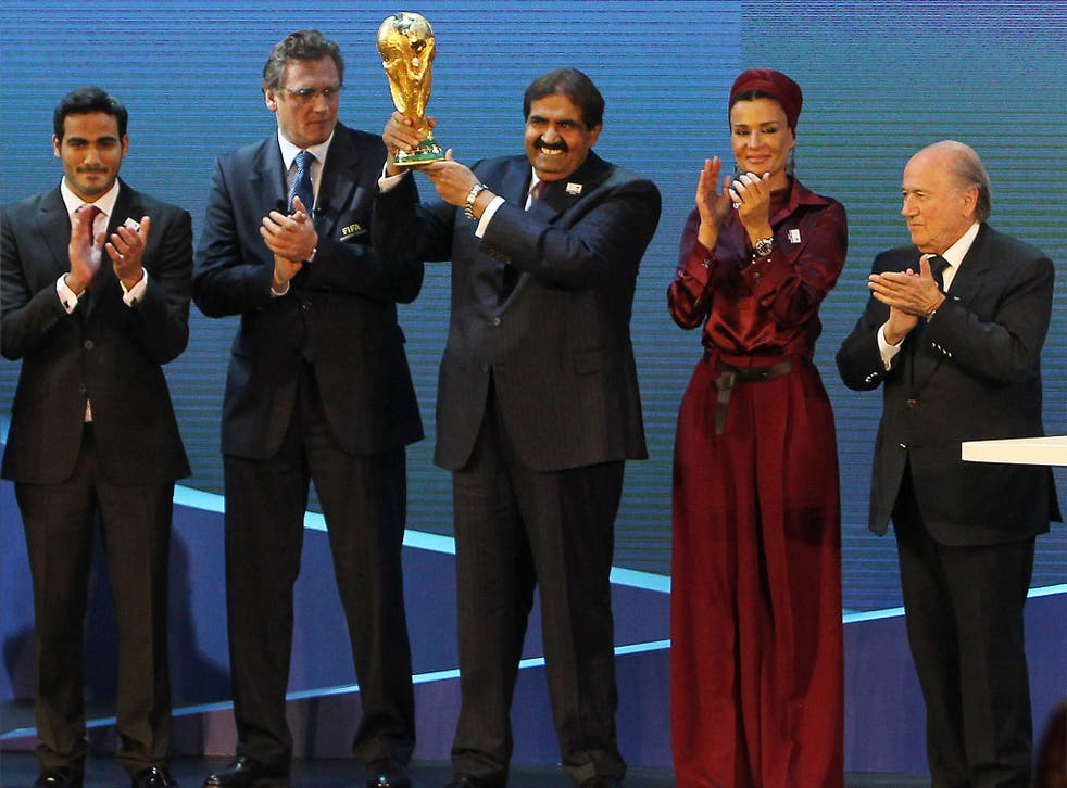 Qatar's Emir Sheikh Hamad bin Khalifa al-Thani raises the World Cup after winning the vote