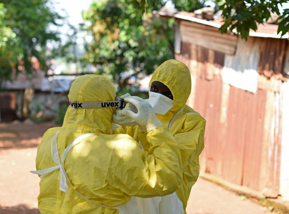 Health workers from Sierra Leone's Red Cross Society Burial Team 7 prepare to remove a body from a house in Freetown on November 12