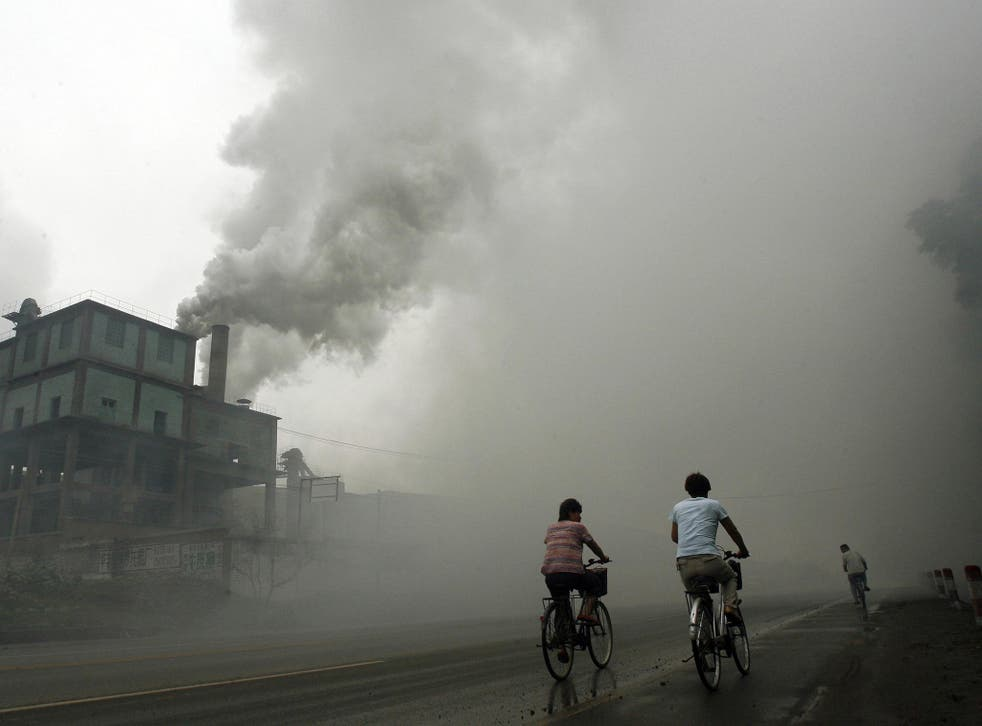 Cyclists pass through thick pollution from a factory in Yutian, 100km east of Beijing in China's northwest Hebei province