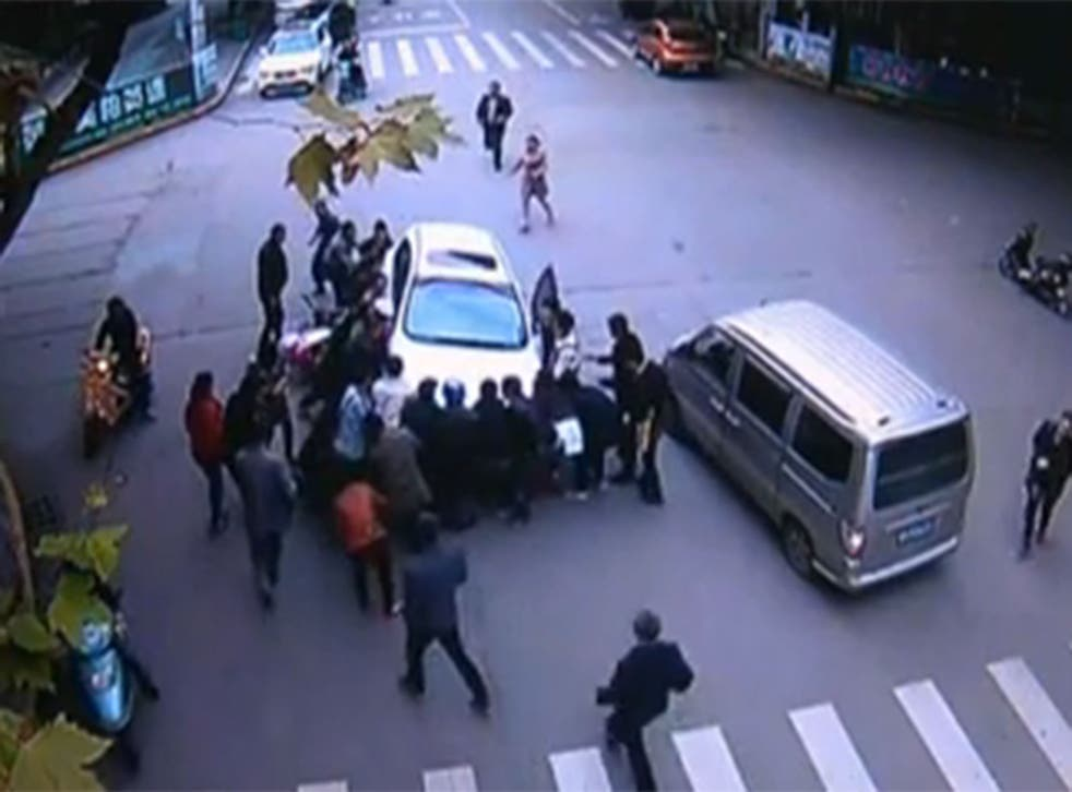 Video from China shows the amazing moment over 20 people rushed to the aid of a woman trapped underneath a car following a crash with the motorbike she was riding on with her husband.