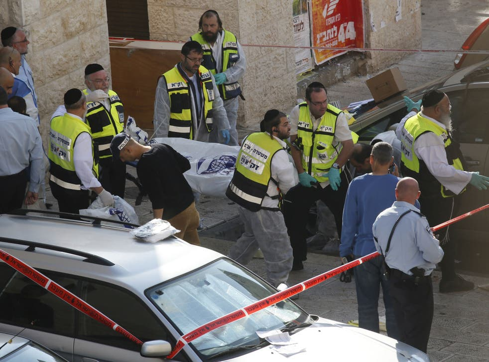 Israeli Zaka emergency services volunteers carry the body of an assailant who was shot dead while attacking a synagogue